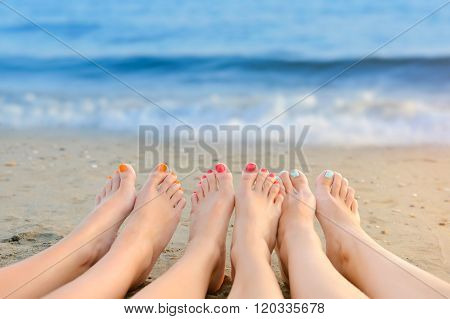 Female Legs With Color Pedicure On The Background Of The Sea
