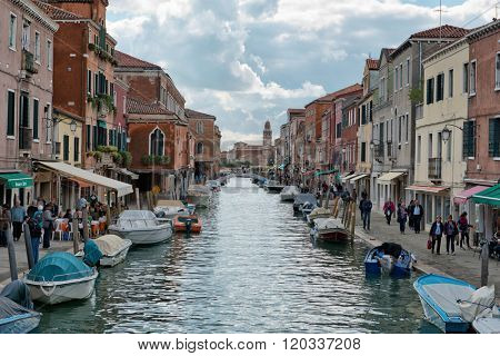 VENICE, ITALY - 17 OCTOBER 2015: Canal scene on the island of Murano, Venice known for its glass manufacturing, with moored boats, tourists and stores, Venice, Italy