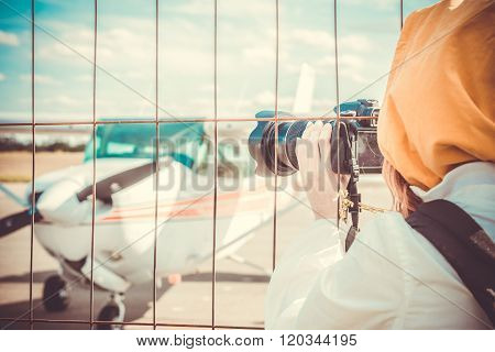 Spotter photographing small plane through the fence of Airport