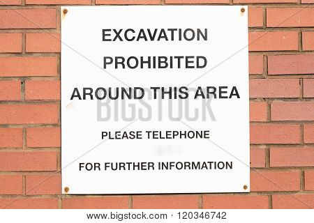 A white sign with the letters 'EXCAVATION PROHIBITED AROUND THIS AREA' with a blank space for a telephone number underneath.