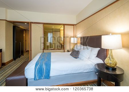 Modern master bedroom in a luxury house hotel with a window into a bathroom. Interior design.