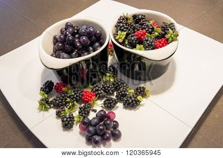 Assorted field berries on a white plate.