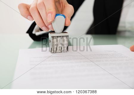 Businesswoman Hand Stamping Paper With Date Stamper
