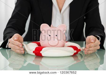 Businesswoman Hand Protecting Piggybank With Lifebelt