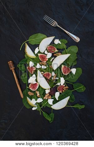 Salad with pears, baby spinach, figs, walnuts, goat cheese and honey on black stone background