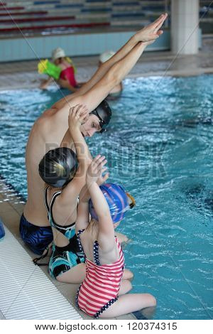 little girls at swimming lesson in indoor swimming pool