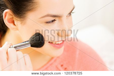beauty, make up, cosmetics and people concept - close up of smiling young woman face applying blush with makeup brush