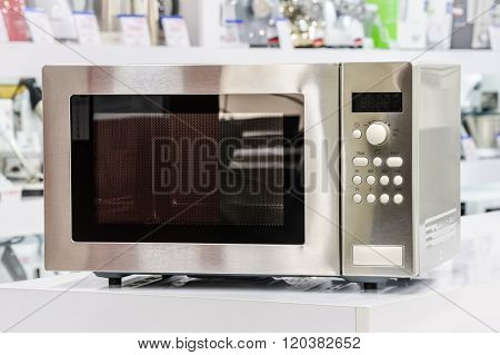 single silver metallic microwave oven at retail store shelf, defocused background