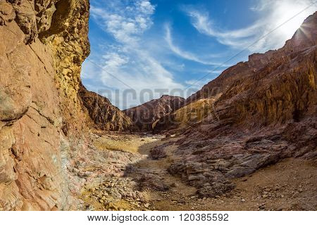 Black canyon in ancient Eilat mountains. Orange and pink sandstone warm glow in the sun.  Photo taken fisheye lens