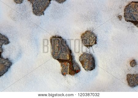 Snow Thawing. Background Of Snow And Stone Blocks.