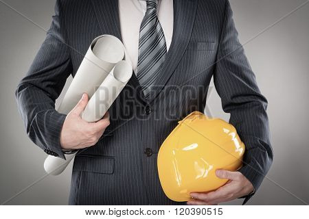 Construction master holding yellow helmet and blueprin
