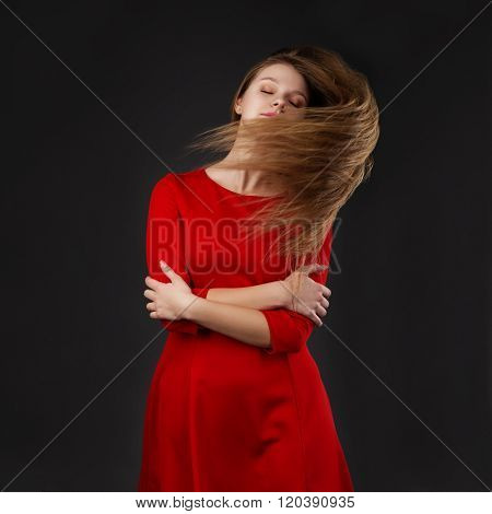 Portrait Of A Young Beautiful Girl With Eyes Closed In A Red Dress With A Flying Hair