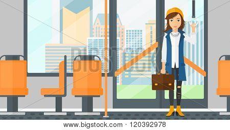 Woman standing inside public transport.
