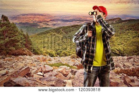 Man finder with binocular standing on stones