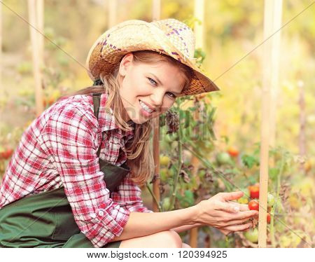 Happy horticulturist woman in straw hat in the backyard.