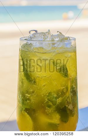background glass of lemonade with ice and mint on the beach