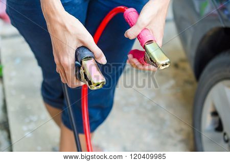 Hand Of Woman Holding Jumper Cable For Recharge The Battery Car