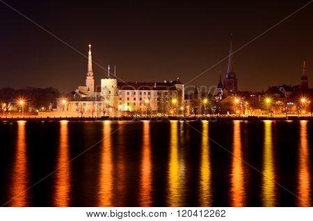 Night panorama of Riga historical centre. Colourful night illumination reflecting in calm Daugava ri