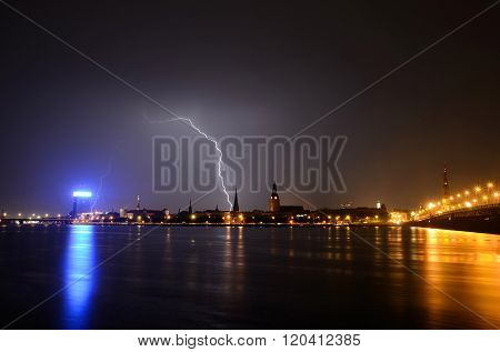 Night Riga panorama with lightning striking a building in historical city centre.