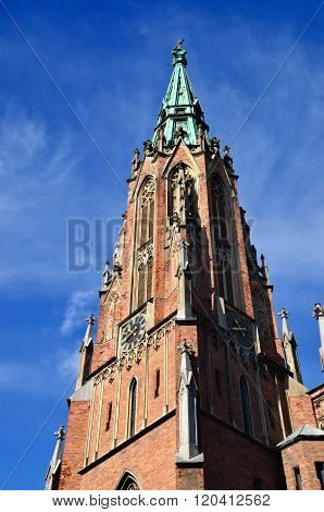 Gertrude church tower in Riga, Latvia, against clear blue sky poster
