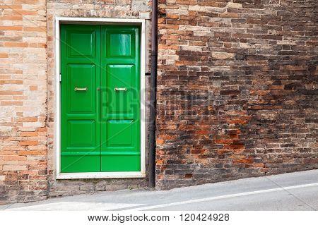 Green Wooden Door In Old Brick Wall