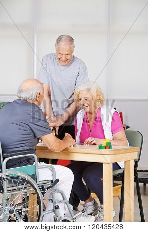 Happy senior people during rehab playing Bingo together