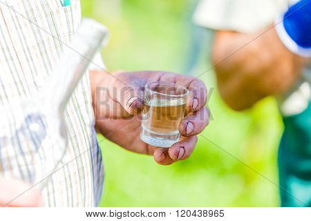 Countryman serving traditional alcoholic beverage - hungarian palinka - when making a pause of work.