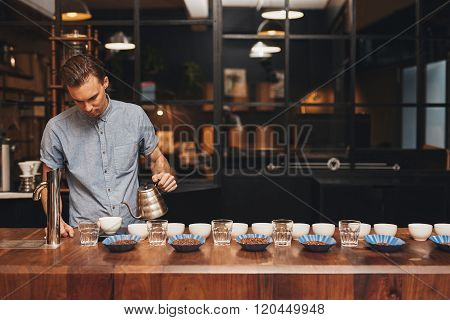Professional barista in a modern roastery preparing for a coffee tasting session, at a wooden counter laid out with neat rows of cups, water glasses and open containers of coffee beans poster