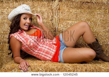 Beautiful smiling cowgirl in hay