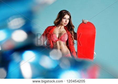 Pretty Fitness Young Woman With Nice Makeup Holding Red Snowboard On Winter Background. Space For Yo