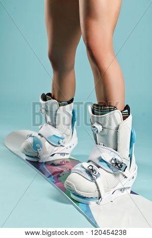 Legs In Snowboard Boots Of Pretty Young Sexy Girl In Bikini On Blue Background. Space For Your Logo.