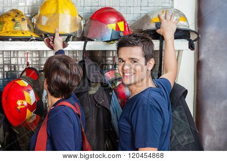 Happy Firefighter With Colleague Removing Helmet