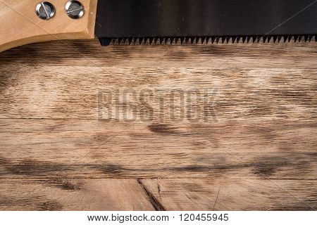 Saw on wooden table. background
