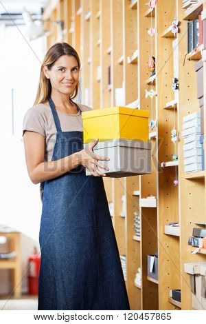 Confident Woman Carrying Boxes In Store