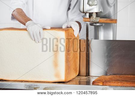 Baker Holding Big Bread Loaf At Cutting Machine In Bakery