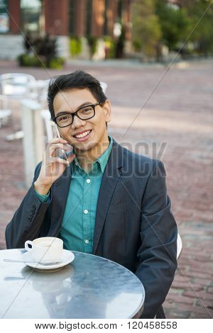 Successful young asian man in business casual attire sitting and smiling in relaxing outdoor cafe with cup of coffee talking on mobile phone