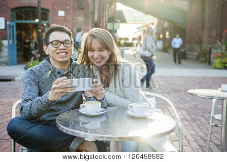 Two laughing young people looking into smartphone while sitting at a table in outdoor cafe