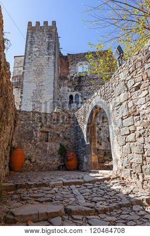 Entrance of the medieval Castle of Leiria with a gothic arch, seen from a narrow passage made of old cobbletones. Leiria, Portugal.