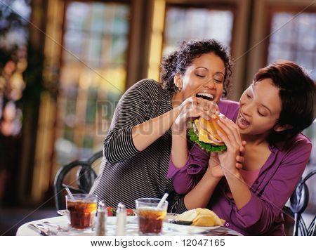 Young women fighting to take bite of hamburger