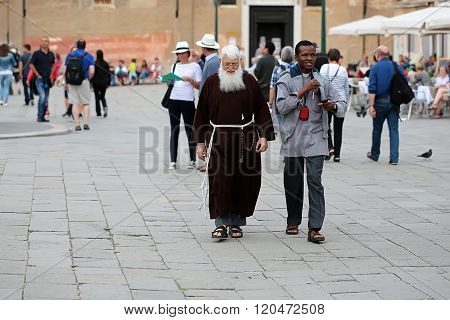 VENICE ITALY - SEPTEMBER 22, 2015: Unidentified priest with grey beard in brown robe with african man walking and speaking along famous venetian square with crowd of tourists outdoor horizontal picture