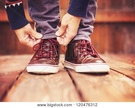 a person tying their shoes on their feet outside on a stained wooden deck toned with a retro vintage filter instagram app or action effect