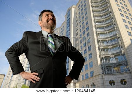 Mature businessman looking up with buildings on the background
