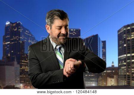 Mature businessman looking at his band wrist with buildings as background