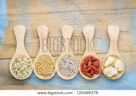 superfood abstract (hemp seeds, golden flax seeds, chia seeds, goji berry, macadamia nuts), top view of  wooden spoons