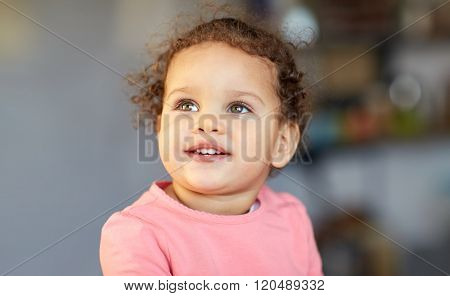 childhood and people concept - beautiful little mulatto baby girl face