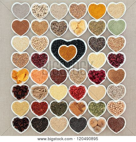 Large dried superfood collection in heart shaped porcelain bowls forming an abstract background over hessian background. High in minerals, vitamins and antioxidants. poster