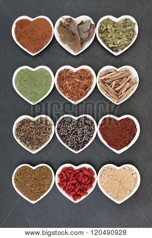 Herbal medicine selection for men in heart shaped white porcelain dishes over slate background.