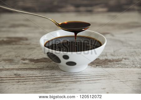 Grape molasses flowing from the spoon on wooden background.