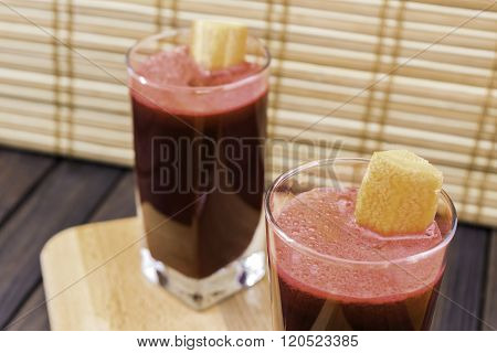 Fresh Carrot And Beetroot Juice In Glass Decorated With Carrot Slices On Wooden Tray And Bamboo Back
