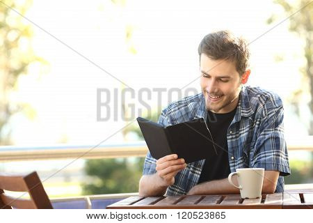 Man Reading A Book In An Ebook Reader